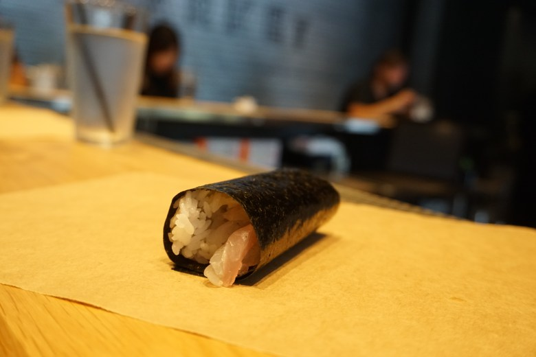 "Photo Description: a ""temaki"" restaurant is serving hosomaki which is a single filling roll. It sits atop a piece of paper, atop the half square shaped sushi bar."