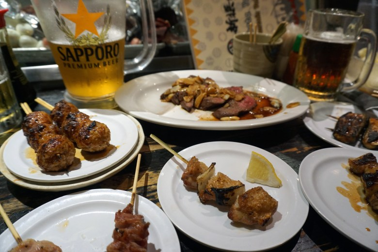 Photo Description: what a spread of different cuts of grilled meat from tsukune, ribye with garlic, chicken thigh and onion, gizzards, garlic, to large pitchers of beer.