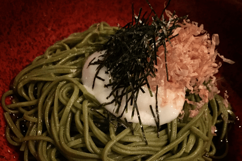 Photo Description: matcha or green tea noodles are in a red round bowl. On top of the noodles is a poached egg, kizami nori, and bonito flakes. At the bottom is a dashi of most likely soy sauce and fish stock.