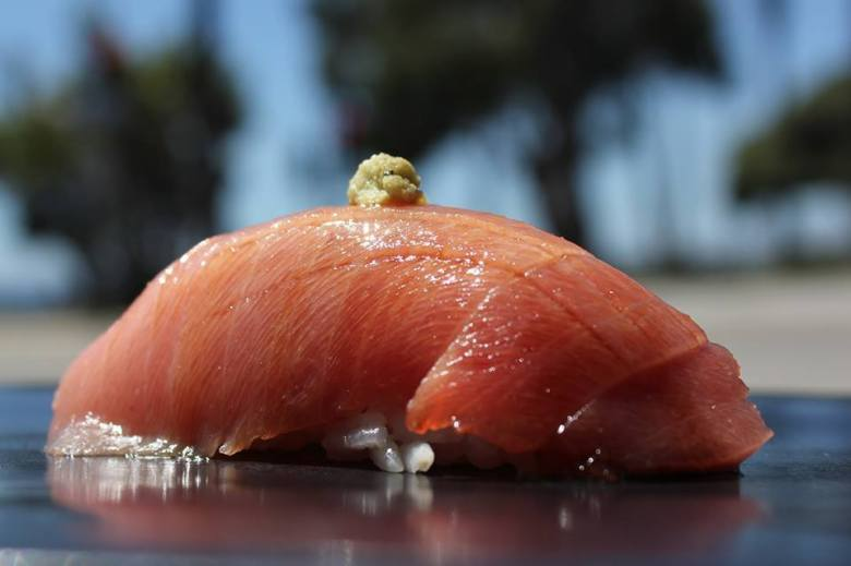 Photo Description: Sushi roku in Newport Beach has a shot of their nigiri sushi with a dab of wasabi sitting atop it. In the background are trees that you can barely make out due to the camera's bokeh.