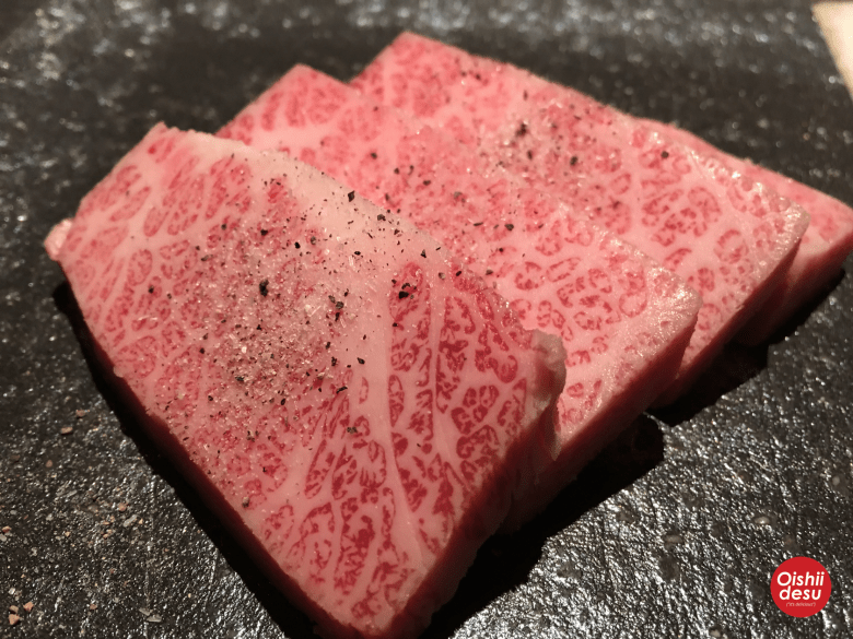 Photo Description: three large prominent slices that look fairly thick exemplify shimofuri because they are well marbled from edge to edge. A sprinkling of what appears to be salt and pepper are atop all three slices.