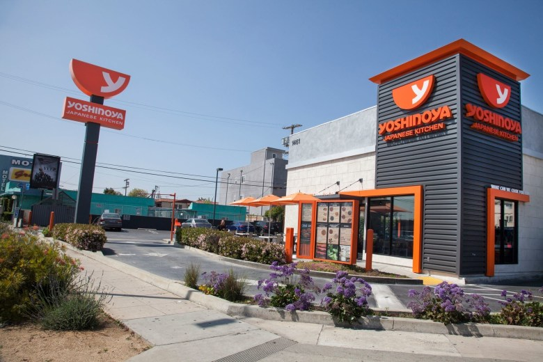 Photo Description: a Yoshinoya location that is of there new design which has their new logo, and building facade of dark grey, light grey, and orange accents.