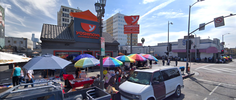 Photo Description: The Yoshinoya on alvarado street via google maps. Surrounding the Yoshinoya is a bunch of street vendors, a busted up Chevy Astro van, a 99 cent store, and a number of people on the street.