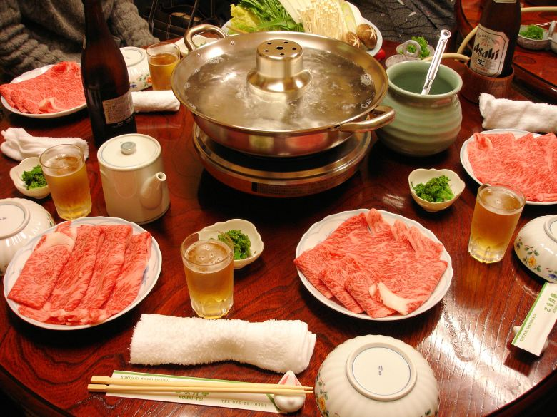 Photo Description: the shabu shabu spread which consists of a large pot of semi-boiling water with konbu in it. Surrounding it a number of smaller plates with very thinly sliced marbled meat. In smaller sauce bowls is piles of green onion. Of in the distance is the plate for of veggies including mushrooms.