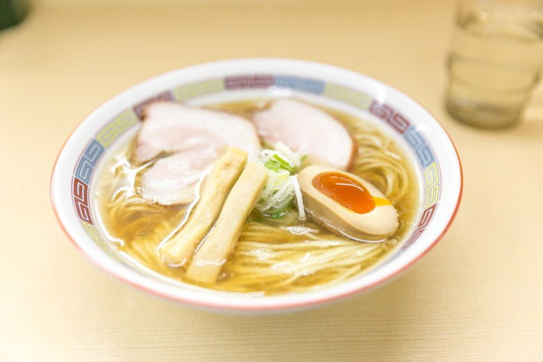 Photo Description: a ramen bowl with the traditional ramen toppings in the bowl. The toppings include chashu (pork), menma (fermented bamboo shoots), aonegi (green onions), and ajitama (marinated egg).