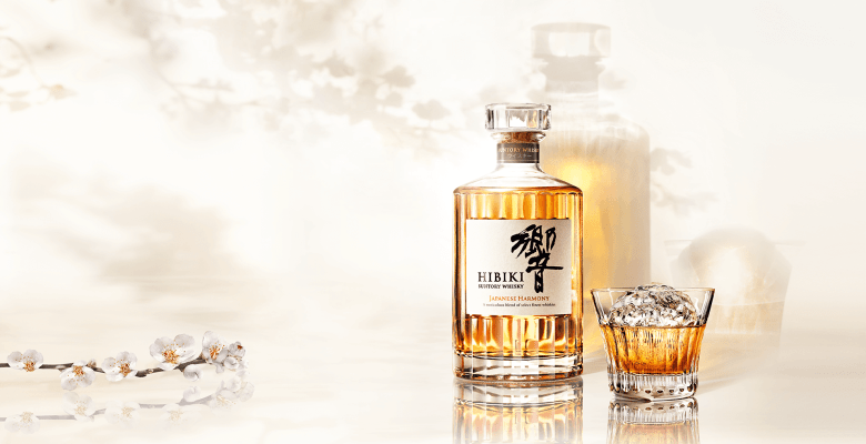 Photo Description: Suntory whisky has a very light image with an image of their Hibiki whisky bottle, a glass with a large ice cube in it, and some white leafed flowers adorning the shot.