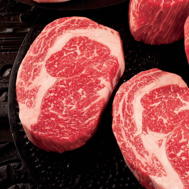 """Photo Description: I chatted with a visually impaired person about how important """"Alt Text"""" is so I will describe the four steaks on a black skillet or plate? The steaks are raw, thick, and fairly well marbled. There's a """"ribbon"""" of fat running down the middle almost encircling the inner cut (I would assume this is a rib-eye)."""