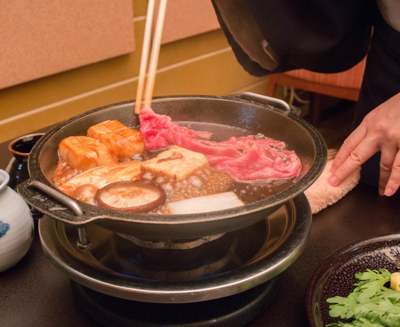 Photo Descriptions: a picture of sukiyaki done right and there is a female assisting in the preparation of sukiyaki. The person in the pic is using rather large and thick chopsticks to the add the meat to the pot. In the pot you can see tofu, the soy sauce broth, shiitake mushrooms, and a number of other unidentified ingredients. On the side it looks to b a plate of shungiku.