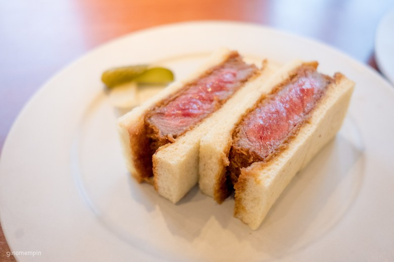 Photo Descriptions: katsu sando sandwiches with shokupan breaad. The sandwich is cut in half, so that you can see the cross section of the medium rare beef katsu. The sandwich sits atop a white round plate.