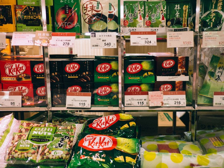 Picture of KitKats in Japan. Several boxes and bags of KitKats displayed at a store with their pricing from 95 yen to 216 yen.