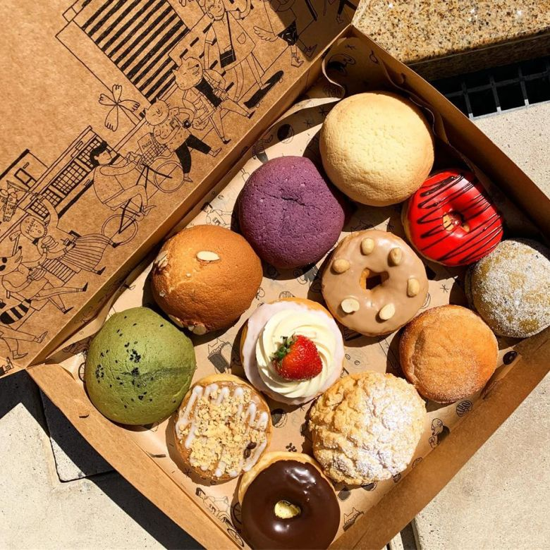 Pictured is a box of pastries. The brown box, has a flip open lid, and on the inside of the lid, there's a illustration of people,. animal characters, cruising along a street.