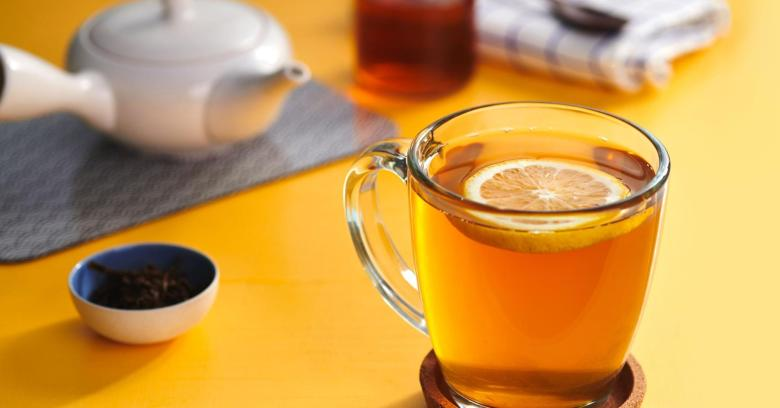 Photo Description: a teapot, a glass with a lemon in it meant to most likely depict hojicha (roasted green tea).