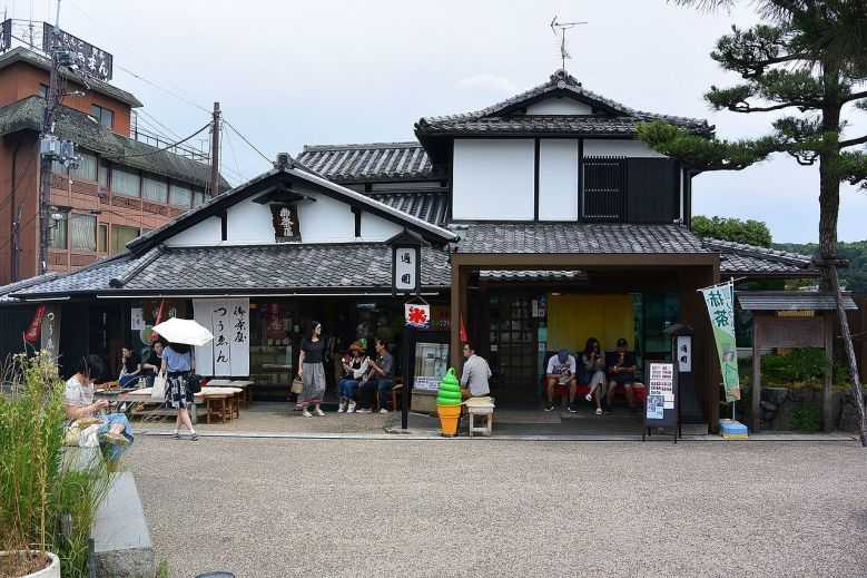 Photo Description: of the oldest teahouse in Japan. The white walled building with black accent has a number of people sitting out front with a bright green soft serve statue in front.