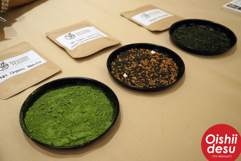 Photo Description: a table with 3 plates placed on it with three packages behind it. In the first is of bright green matcha powder, genmaicha, and another of tea leaves.