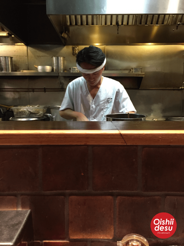 Photo description: a chef from Tsujita Ramen standing behind the counter looking down at something as he works with the counter in the foreground separating guests from the open kitchen