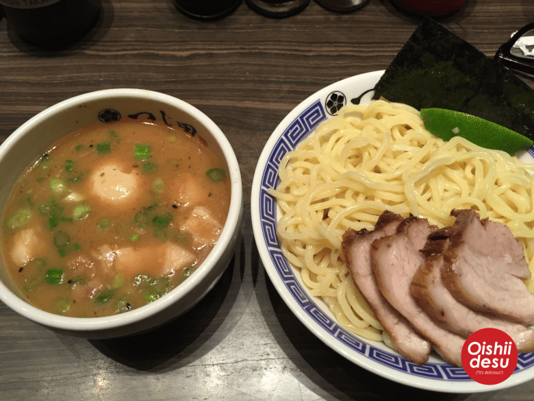 Photo Description: two bowls that make up tsukemen, one with the soup broth to dip the noodles in and the other of the noodles. The noodle bowl has the noodles, char siu, a lime, and sheet of black nori laid against the edge of the bowl