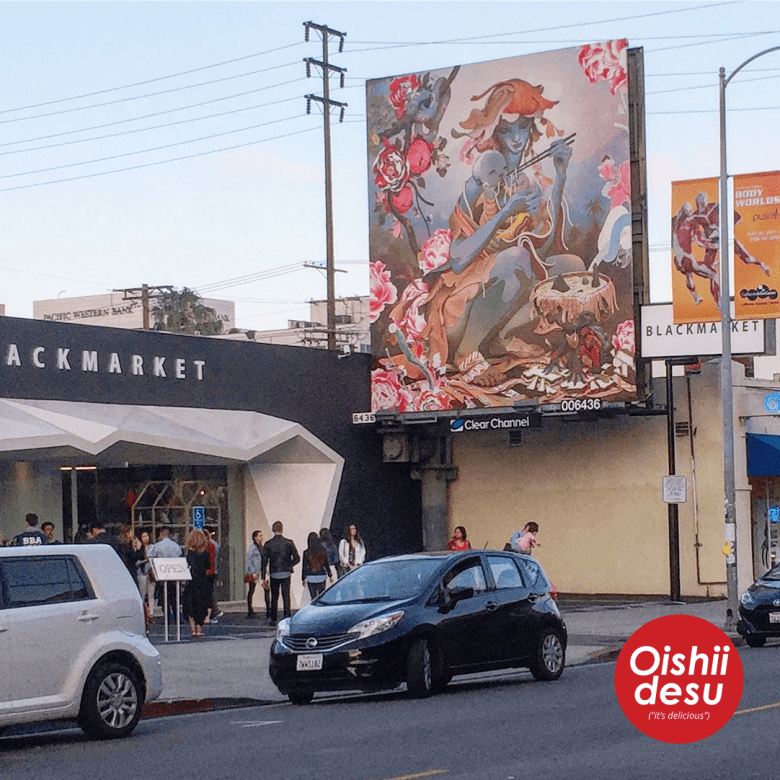 Photo Description: Sawtelle Blvd with people standing out front of the Black Market retail store with a giant sign above them of an artistic surreal billboard with a blue female looking figure with chopsticks feeding its baby
