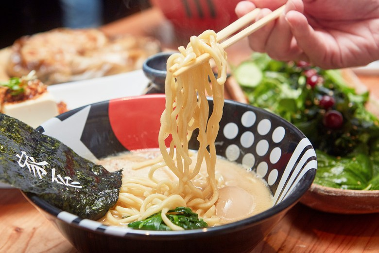 Photo Description: EAK ramen with their funky art deco looking bowl with bold black, white and red graphics. In the bowl, thick noodlels, spinach, an egg, and nori (seaweed).