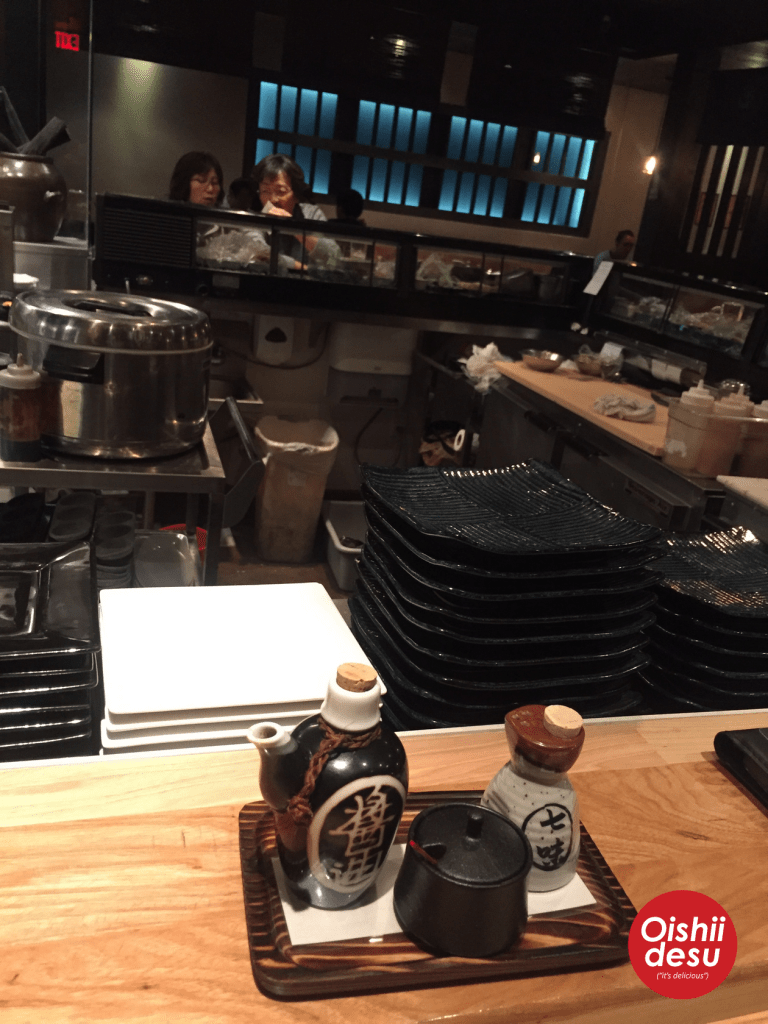 Photo Description: at the bar, you can see behind the scenes. In this shot the sauce squeeze bottles, the rice warmer, along with all their plates which are ceramic, glossy, and either black or white.