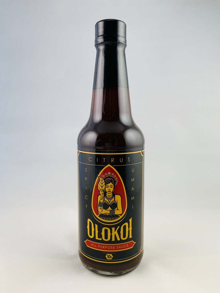 Photo Description: a black beer bottle looking bottle with a very nice gold border, the dark maroon accents, and the girl holding the leaf. The words 10g is on the bottle.