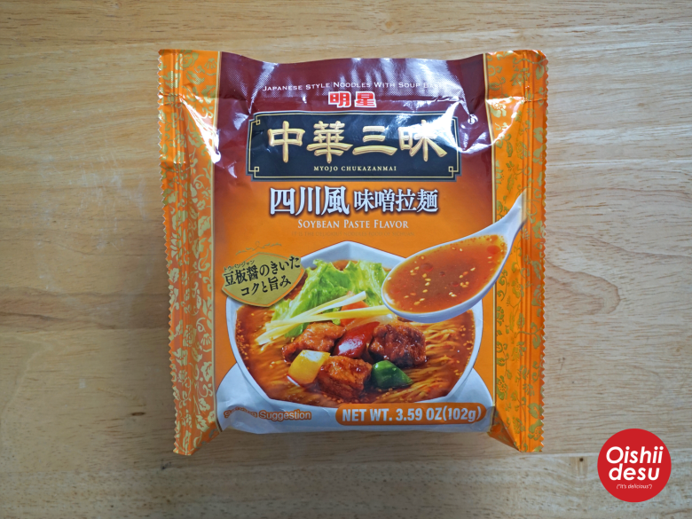 Photo Description: Myojo Chukazanmai miso ramen packaging which is yellowish orange with a pic of a bowl of noodles, and a number of other ingredients.