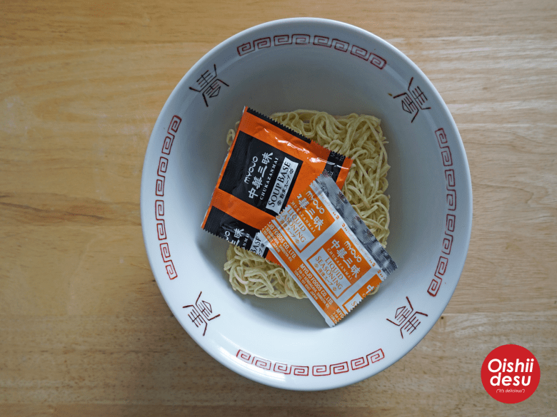 Photo Description: the square block of noodles, the 2 spice packets, and the traditional Chinese style ramen bowl.