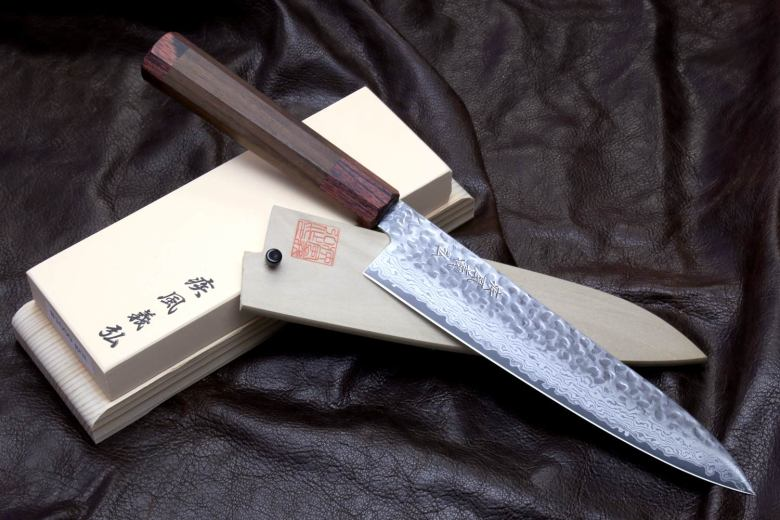 Photo Description: a pic of a Yoshihiro knife atop a sharpening stone set against a black background.
