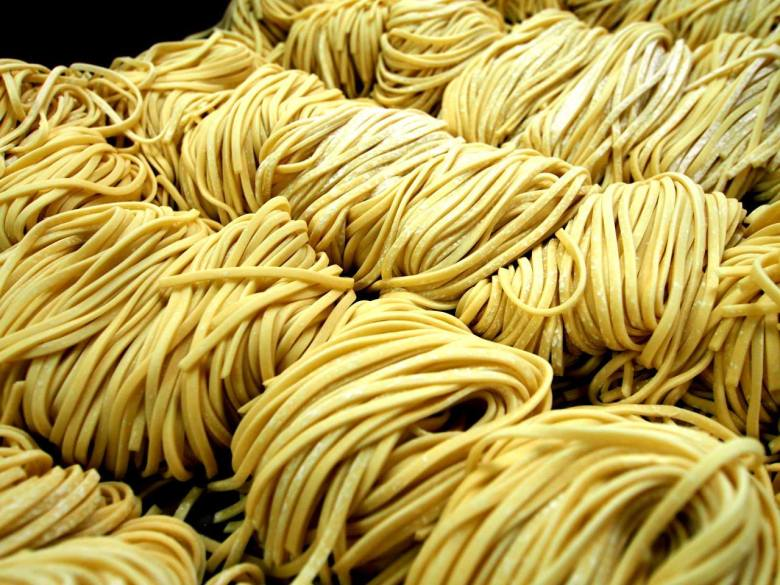Photo description: bundles and rows and rows of fresh ramen noodles. Golden yellow strans of noodles are neatly bunched together with a slight dusting of flour.