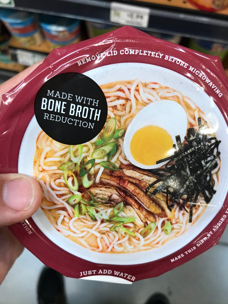 "Photo Description: a pic of me holding the container looking at the lid. The lid has a ""made with bone broth reduction"" label and the picture has the noodles, green onions, nori, and egg."