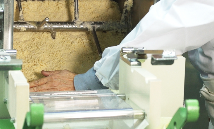 Photo Description: Noodle making machine churning ramen noodle flour in the mixer. An operator's hands can be seen guiding the flour.
