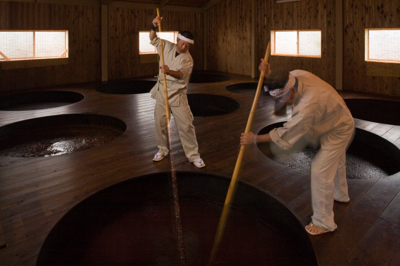 Photo Description: two Japanese men dressed in traditional attire that are off white clothing and white headbands. They are in a room made completely out of wood with several large round holes which are large vats for brewing soy sauce. The two men are using large wooden paddles to most likely stir the concoction below.