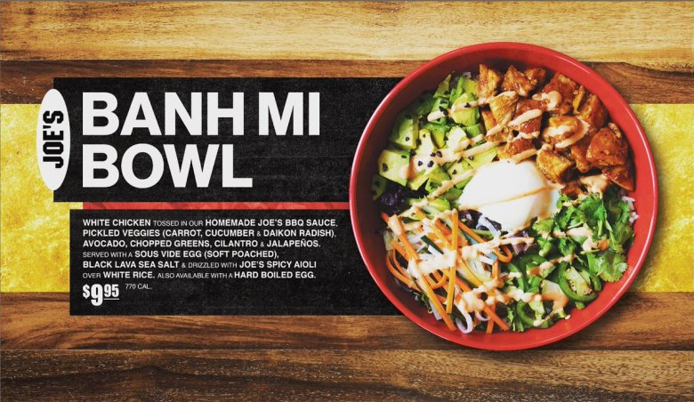 Photo Description: Tokyo Joe's Banh Mi bowl. A red bowl is depicted, shot from directly above, in the bowl what looks to be a poached egg, pickled veggies, avocado, chopped greens, and chicken.