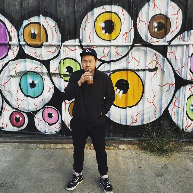 Photo Description: Kero One standing in front of a mural of eyeballs on a black background. The eyes are bloodshot with various colored eyes from yellow, green, brown, to blue.