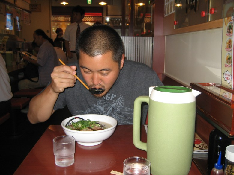 Photo Description: In 2007 in Osaka, Japan, Greg is slurping out of a large spoon as he sits over a bowl of tonkotsu ramen. The bowl is a white bowl with a pile of green onion, and a green table thermos of water is in the foreground.