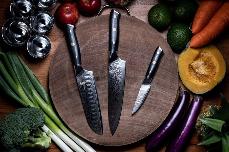 Photo Description: a shot of 3 knives. One of which looks like a kitchen knife, a santoku knife, and possibly a paring knife. Thye are placed on a round cutting board surrounded by an assortment of vegetables from avocado, carrots, eggplant leeks, apples, to a pineapple.