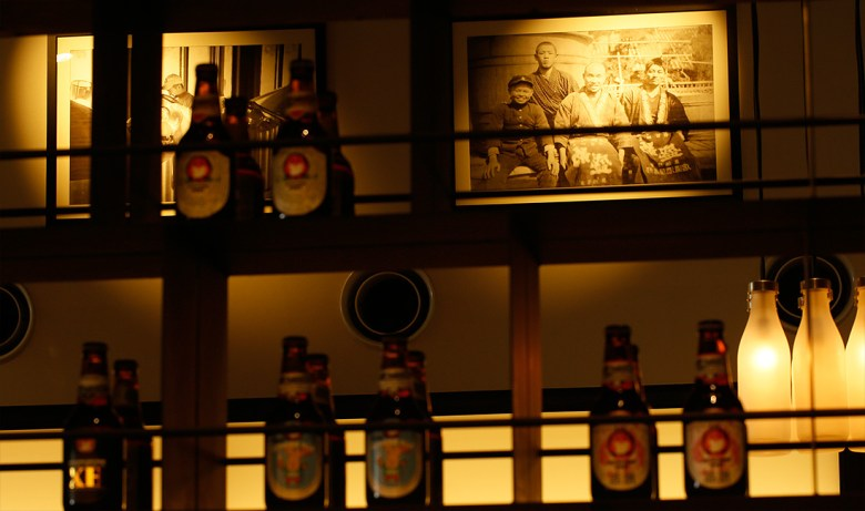 Photo Description: a bar setting in a dark lit room with golden hues shining down on the picture frame of the family, along with several bottles of Hitachino beer.