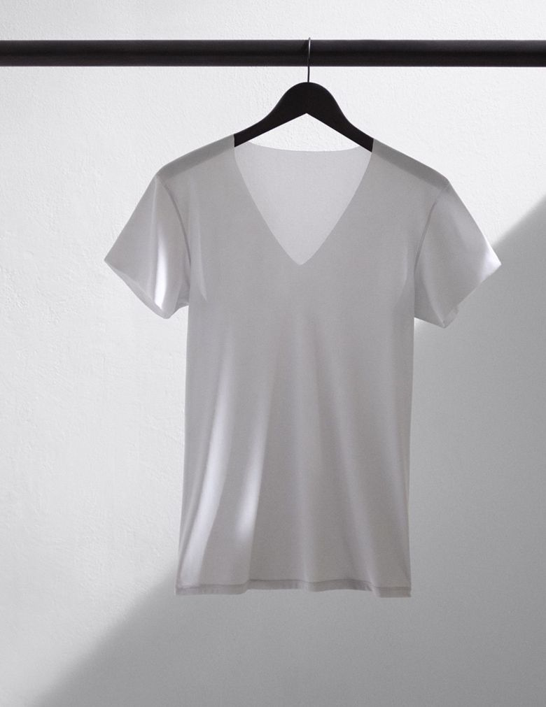 Photo Description: a white UNIQLO AIRism t-shirt hung up on a black hanger in a white room.