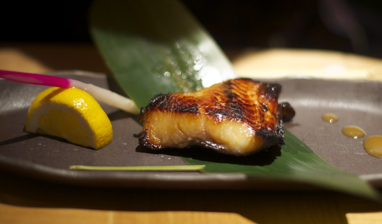 Photo Description: Nobu Matsuhisa's infamous marinated miso black cod dish. It is plated on greyish plate with a slice of lemon.