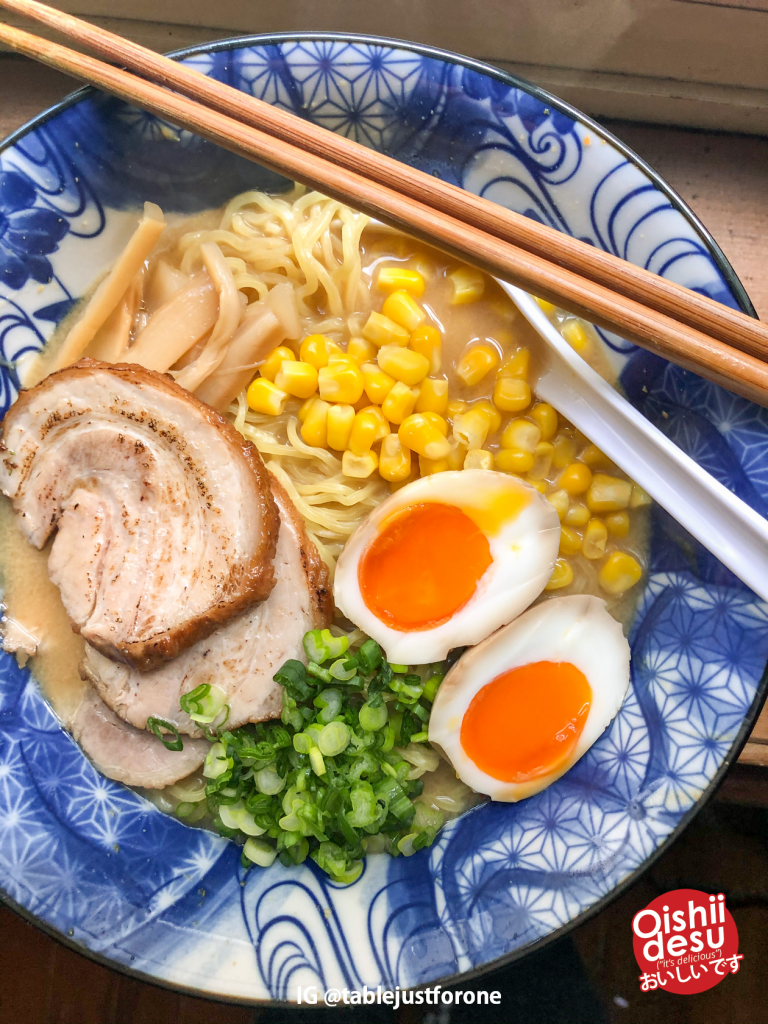 Photo Description: a final product shot of the completed ramen bowl of miso ramen by Jackie. Her bowl has chashu, menma, corn, negi (green onion), and hanjuku (tamago).
