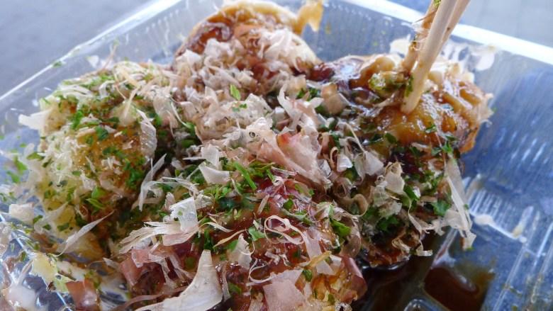 Photo Description: finished takoyaki with bonito flakes, negi (green onions), takoyaki sauce in Osaka Japan.