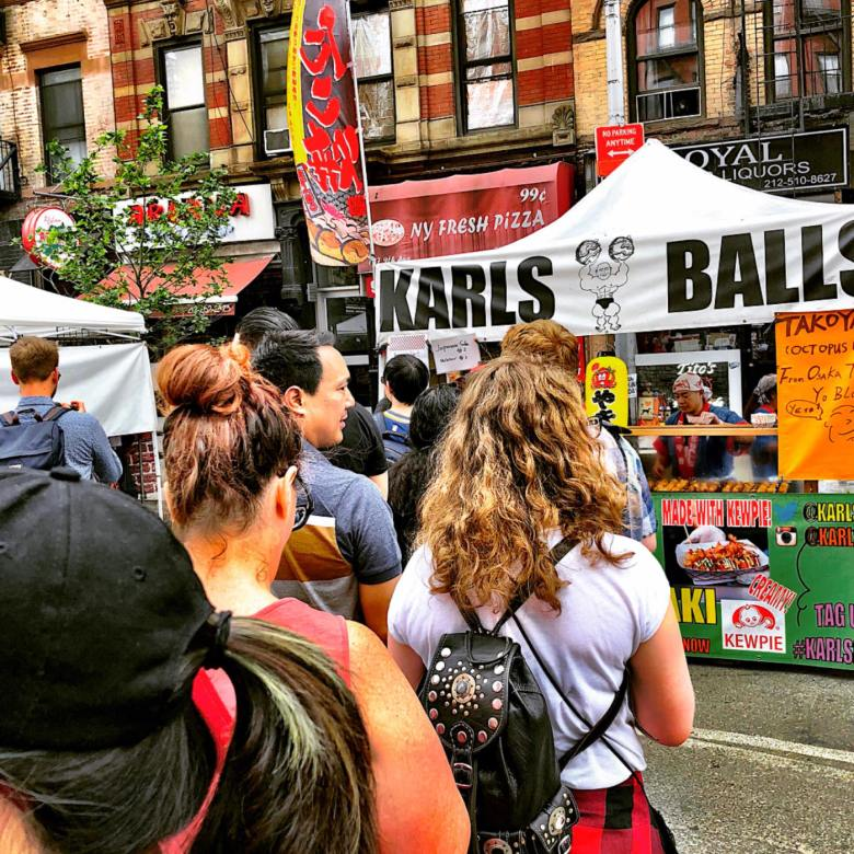 Photo Description: outdoor event, the Karl's Balls white canopy. There's a long line, lined up in front the booth.