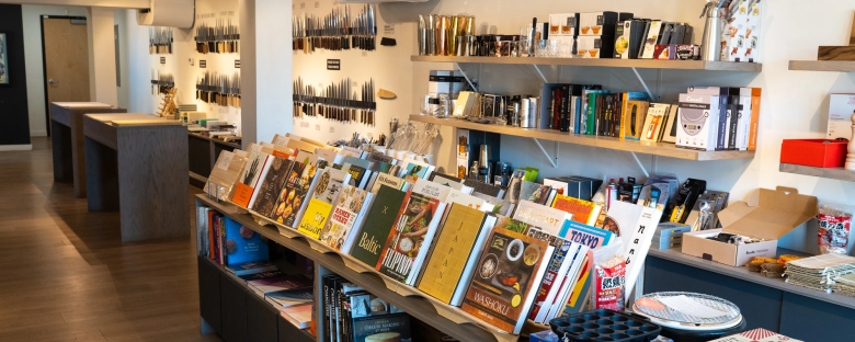 Photo Description: located on Larimer in the five points neighborhood is Carbon Knife. A very clean contemporary look to it with a clean layout which has a number of knives and books displayed.