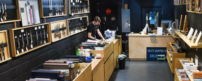 Photo Description: The second most bold interior is Seisuke Knife in Portland, OR. The black walls are offset with a light pine looking boxes bodly display a number of knives vertically in their case.