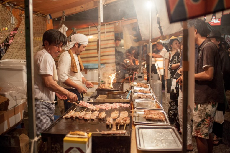 Photo Description: that is how they do it in Japan at an outdoor festival of some sort. Two guys are operating a small booth with several types of yakitori and a number of people gathered around.