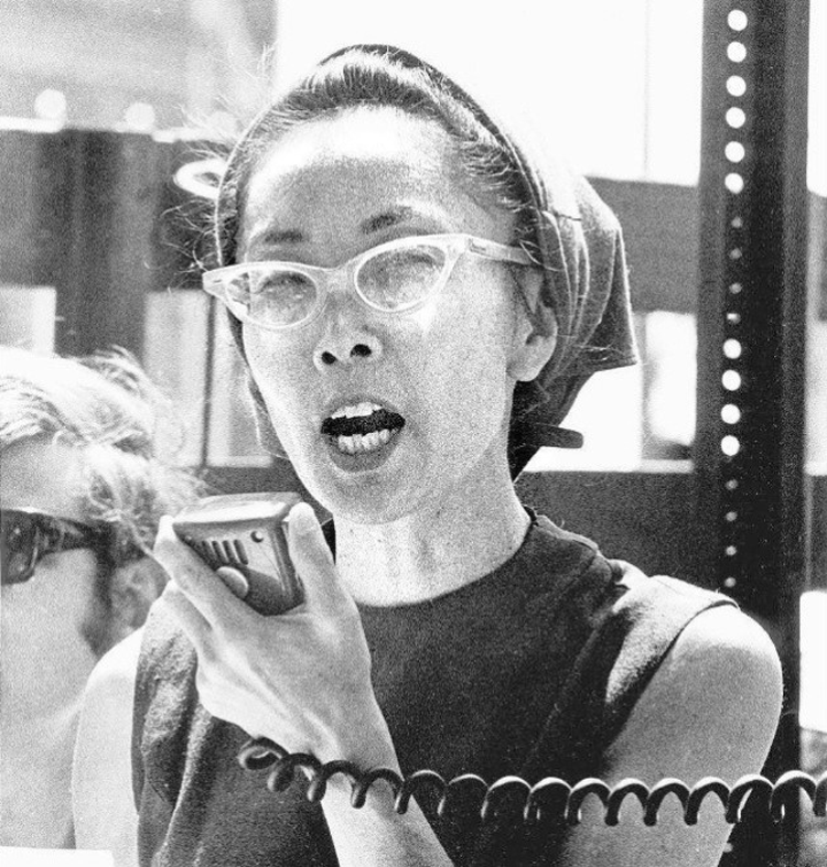Photo Description: the most common pic of Yuri Kochiyama where she is speaking into a microphone, while wearing tear drop shaped glasses, and a rag over her head.