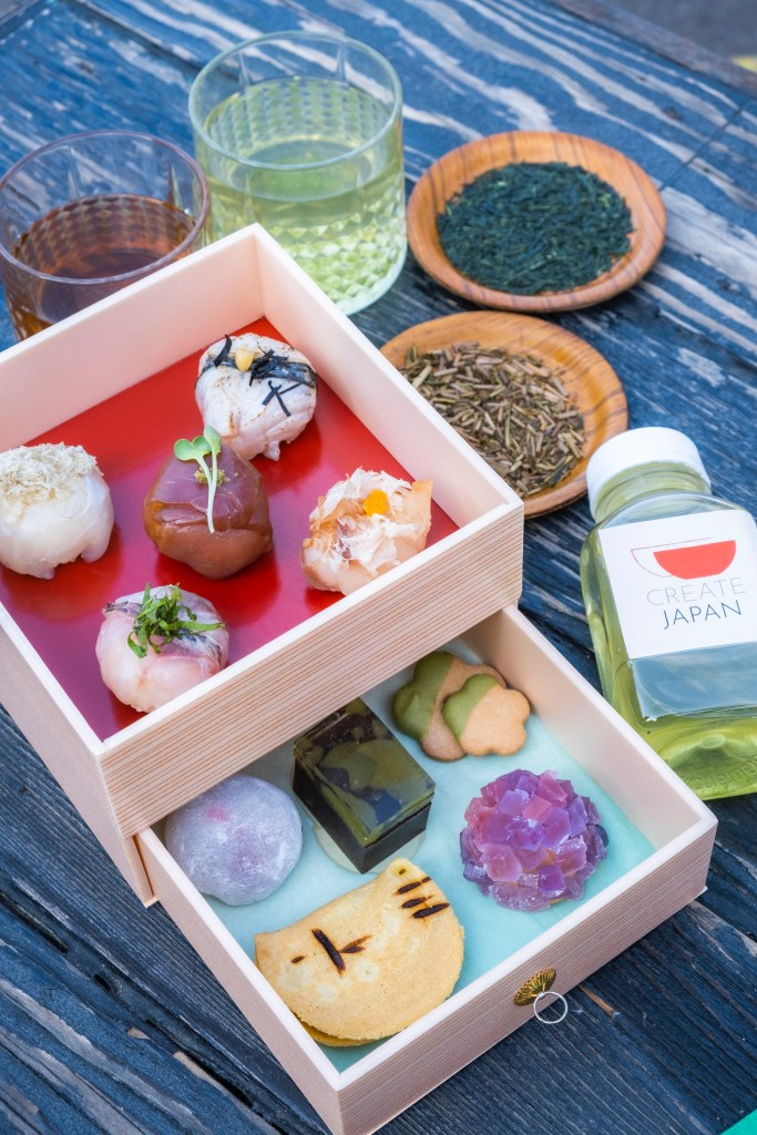 Photo Description: two pine-looking boxes have several food items place in the box. On the side are a couple of round plates with tea leaves in it (they look like hojicha and green tea)