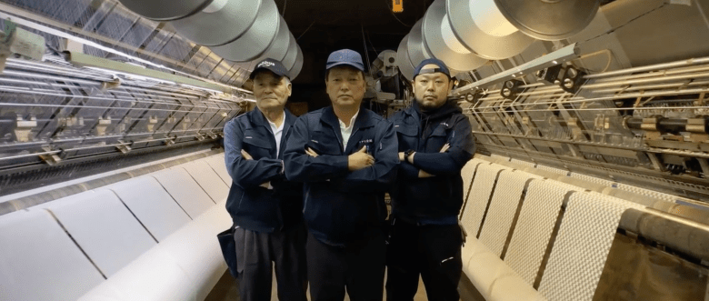 """Photo Description: 3 dudes looking all NWA with 3 baseball style caps, all dark colored, and all three are dressed the same. On either side are large """"loom"""" machines with thread/material on either side of them."""