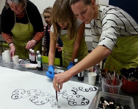 opi - koulutuspalvelut, kuvassa ihmisiä maalaamassa yhdessä koulutus-tilanteessa