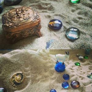 johdatus hiekkakuvaterapiaan kurssin kuvituskuva kuvassa hiekassa pikkuesineitä kuten aarrearkku