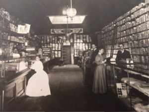 George W. Mallory standing behind counter on the right. This photo was taken in 1905 of the Mallory - Dennison Store.